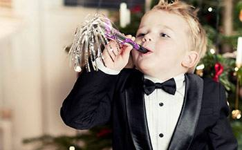 A young boy wearing a black tuxedo holds a New Year's noisemaker