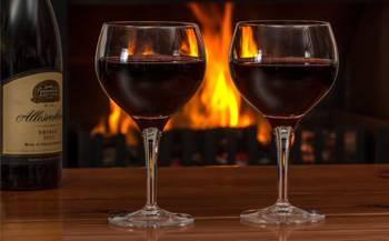 Two wine glasses filled with red wine along with a wine bottle sitting on top of a wooden table with a fireplace in the background