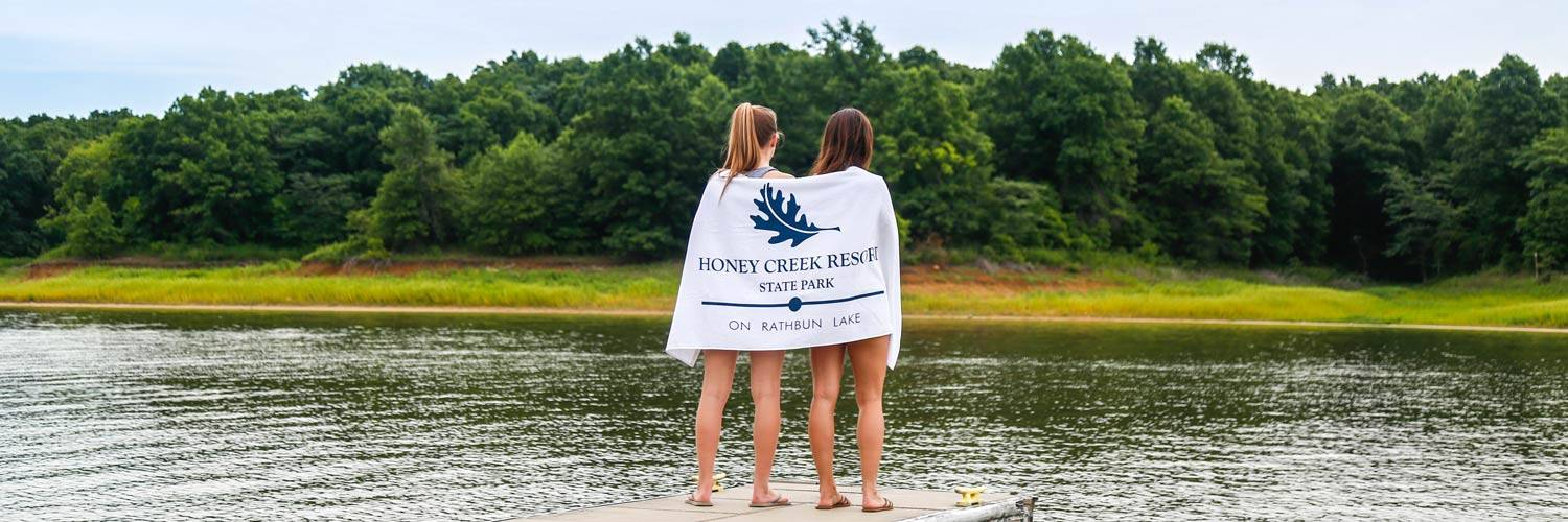 Girls wrapped in a Honey Creek Resort towel standing at the dock on Rathbun Lake