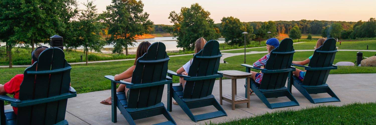 People relaxing in adirondack chairs at Honey Creek Resort looking out at Rathbun Lake