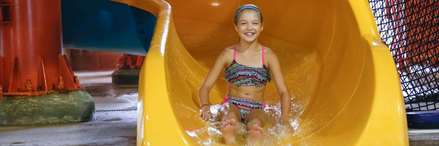 Girl on a water slide at Buccaneer Bay, the Indoor water park at Honey Creek Resort