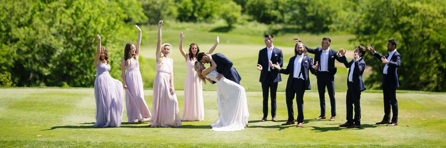Wedding party celebrates the bride and groom on the lawn at Honey Creek Resort in Iowa