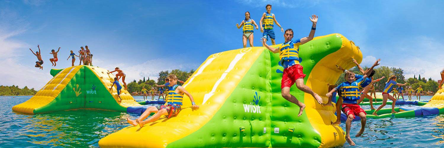 Kids play in an aquapark inflatable waterpark on a lake