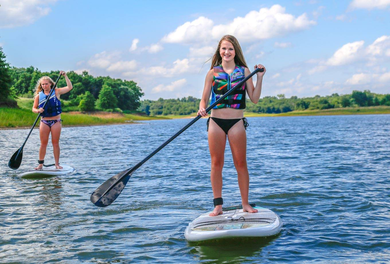 Girls enjoy stand-up paddleboarding on Rathbun Lake with SUP rentals from Honey Creek Resort