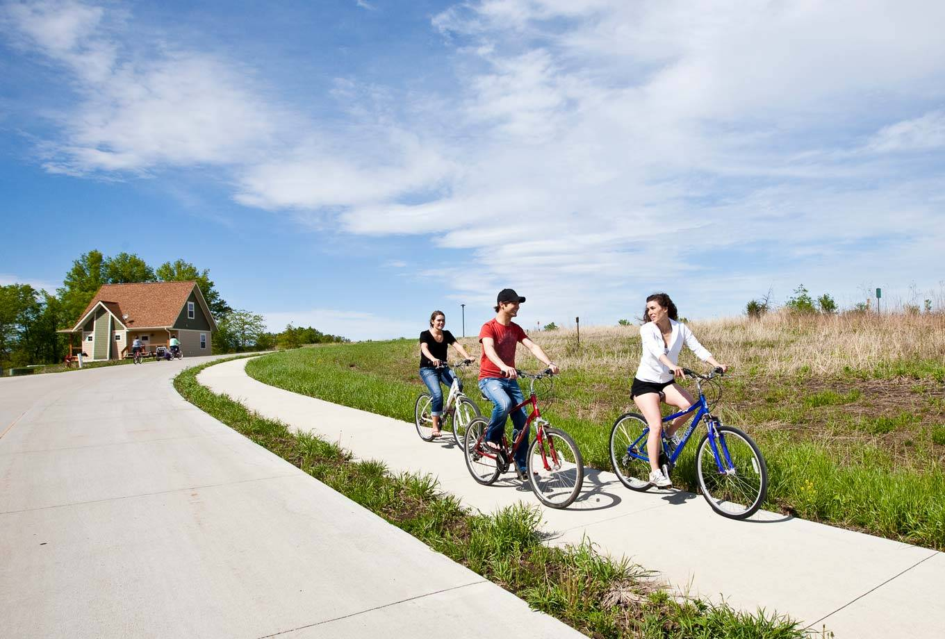 Biking on the trails in front of a cottage at Honey Creek Resort with rental bikes