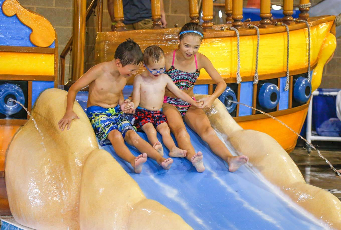 Three kids ready to slide into the water at the indoor water park, Bucanneer Bay, at Honey Creek Resort