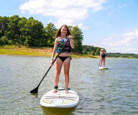 People enjoy fun activities like stand up paddleboarding on Rathbun Lake
