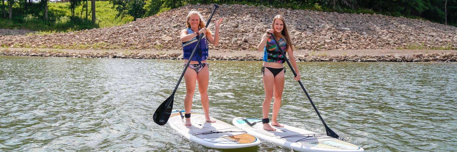 Guests enjoy stand up paddleboarding on Rathbun Lake at Honey Creek Resort