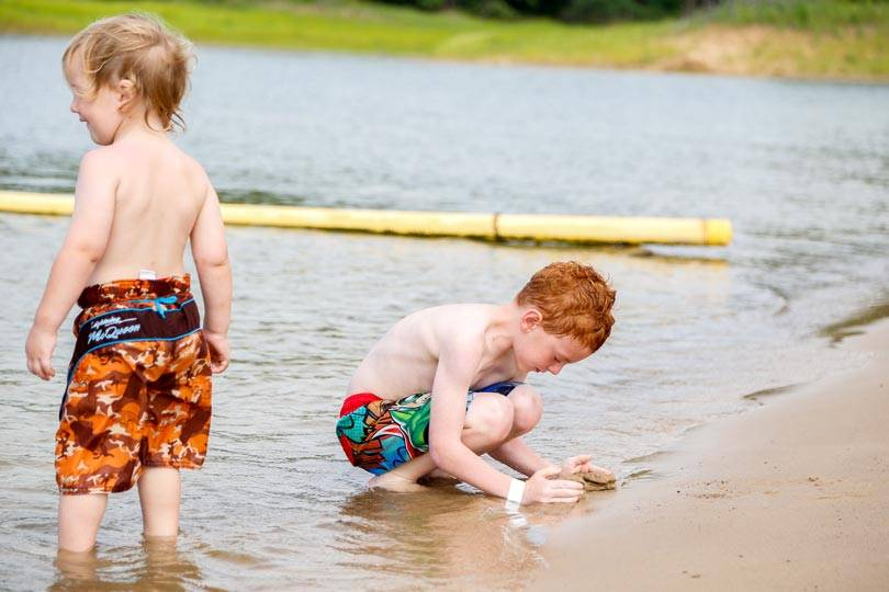 Kids play along the Rathbun Lake shoreline at Honey Creek Resort