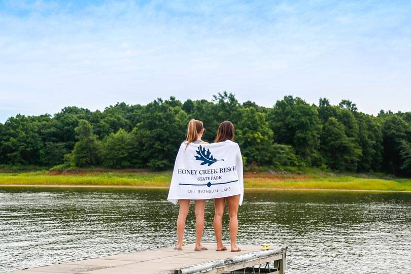 Two girls hold Honey Creek Resort towels on the marina docks at Rathbun Lake