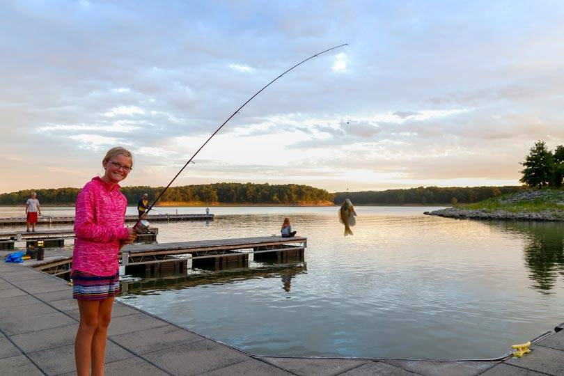 A girl enjoys fishing on Rathbun Lake from the marina docks at Honey Creek Resort