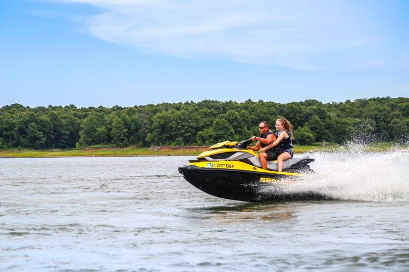 A father and daughter go jet skiing on Rathbun Lake at Honey Creek Resort