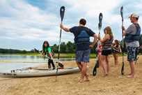 A group of friends participate in a kayak class along Rathbun Lake at Honey Creek Resort