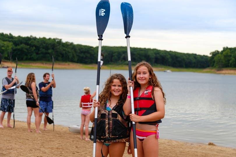 Girls get ready to go stand-up paddleboarding on Rathbun Lake at Honey Creek Resort