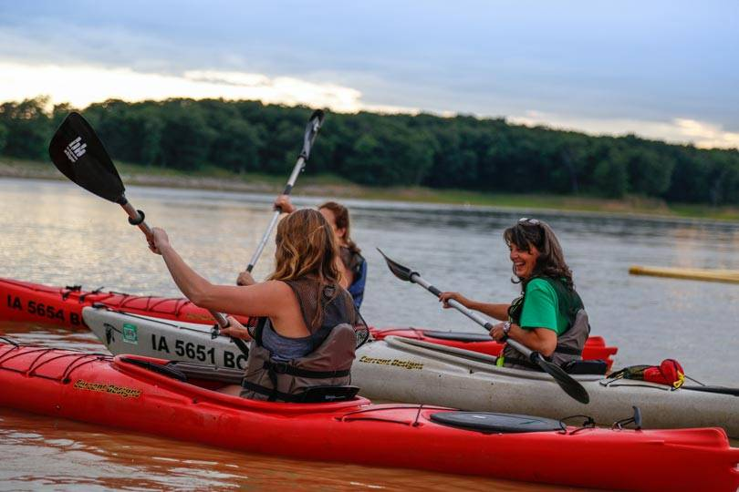 A group of people take a kayaking class at sunset together on Rathbun Lake at Honey Creek Resort