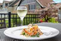 Delicious dining option featuring shrimp served outdoors with a glass of white wine at Rathbun Lakeshore Grille restaurant at Honey Creek Resort