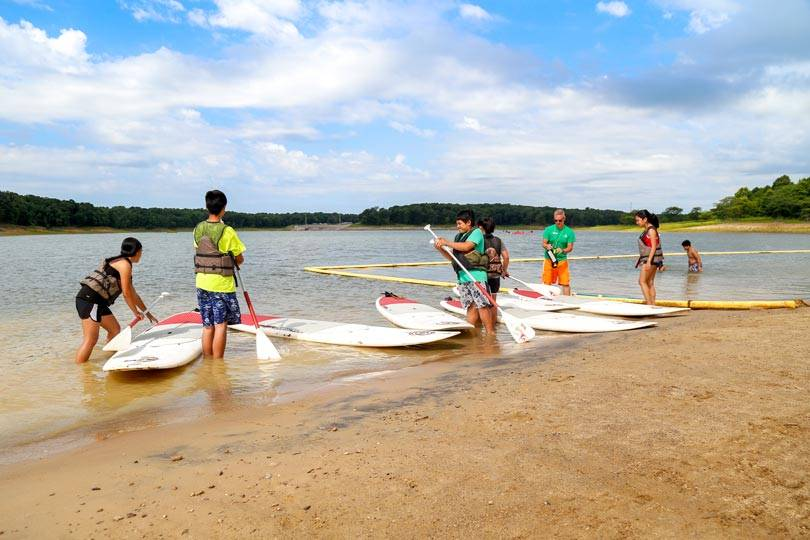 A group of friends receive instruction on how to use stand up paddleboards on Rathbun Lake
