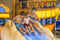 Kids get ready to go down a water slide at Buccaneer Bay, the Indoor water park at Honey Creek Resort