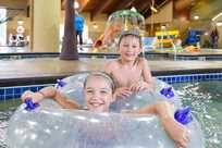 Kids enjoy playing on inner tubes at Bucaneer Bay, the indoor water park at Honey Creek Resort