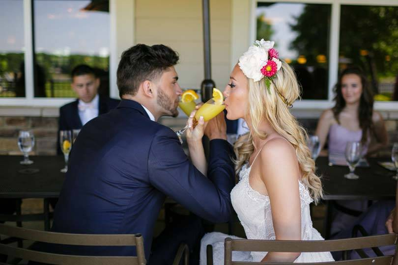 Bride and groom sharing drinks at their Honey Creek Resort wedding