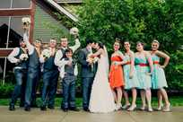 The groomsmen hold the bouquets in this fun wedding party photo at Honey Creek Resort