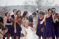 Winter wedding bridal party taking pictures in the snow at Honey Creek Resort