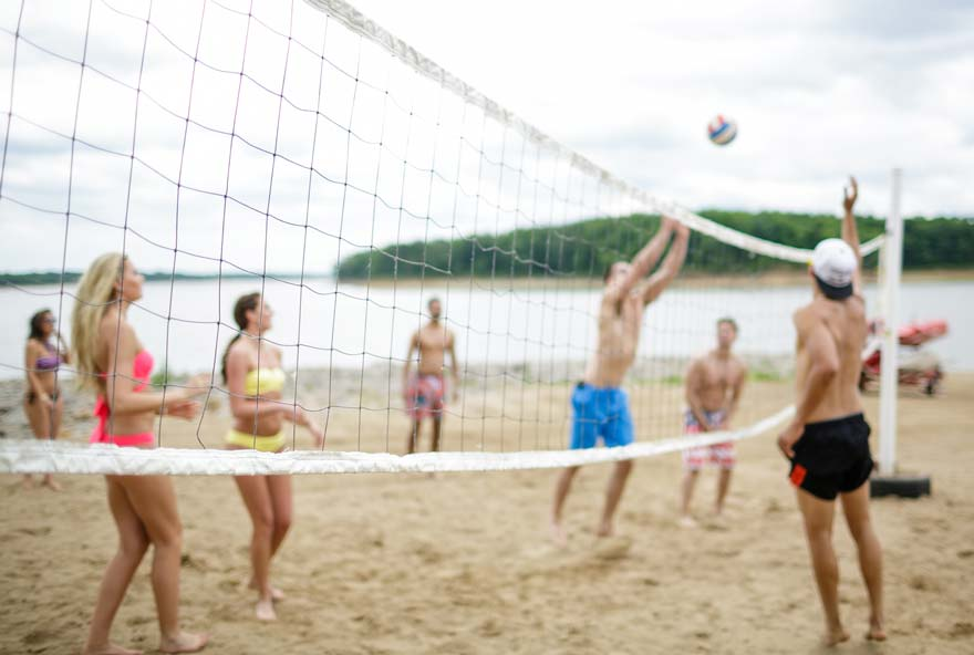 Group of friends playing volleyball on the beach at Honey Creek Resort