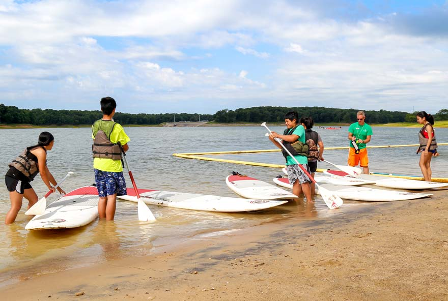 A group of friends prepare to use stand up paddleboards on Rathbun Lake