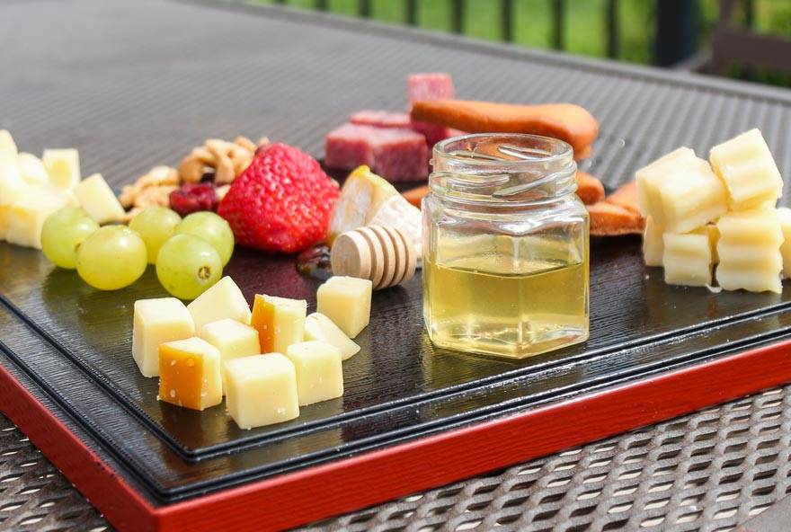 Fruit, cheese, and honey are served on a tray at Honey Creek Resort