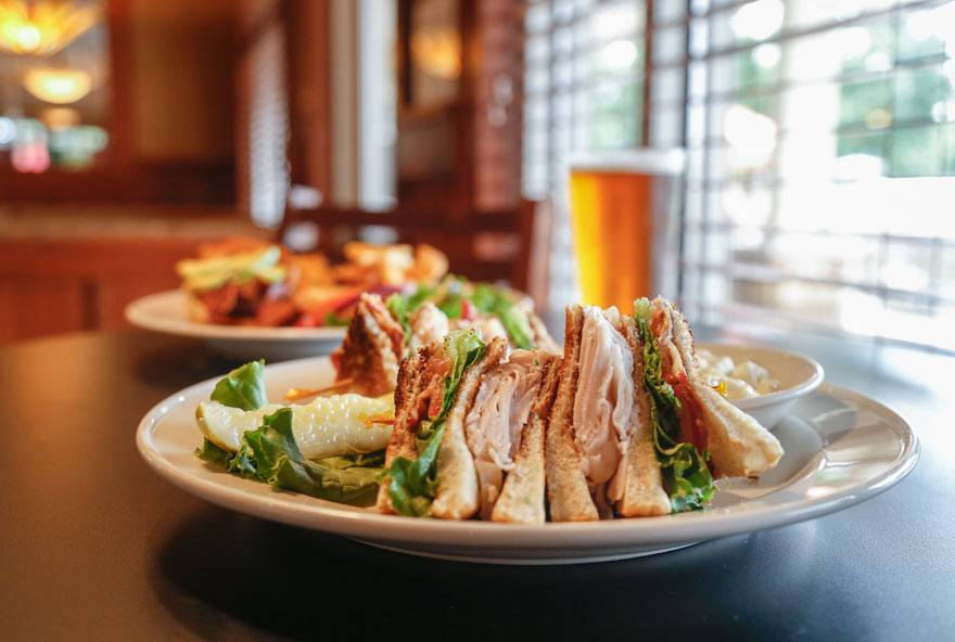 A club sandwich is served on a plate at Rathbun Lakeshore Grille at Honey Creek Resort