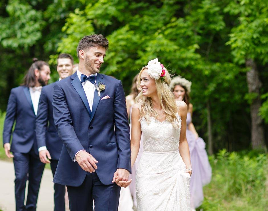 Happy newlyweds walk hand-in-hand after their wedding ceremony at Honey Creek Resort