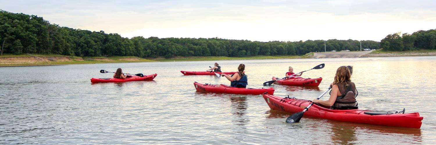 A group of people enjoy kayaking together on Rathbun Lake at Honey Creek Resort