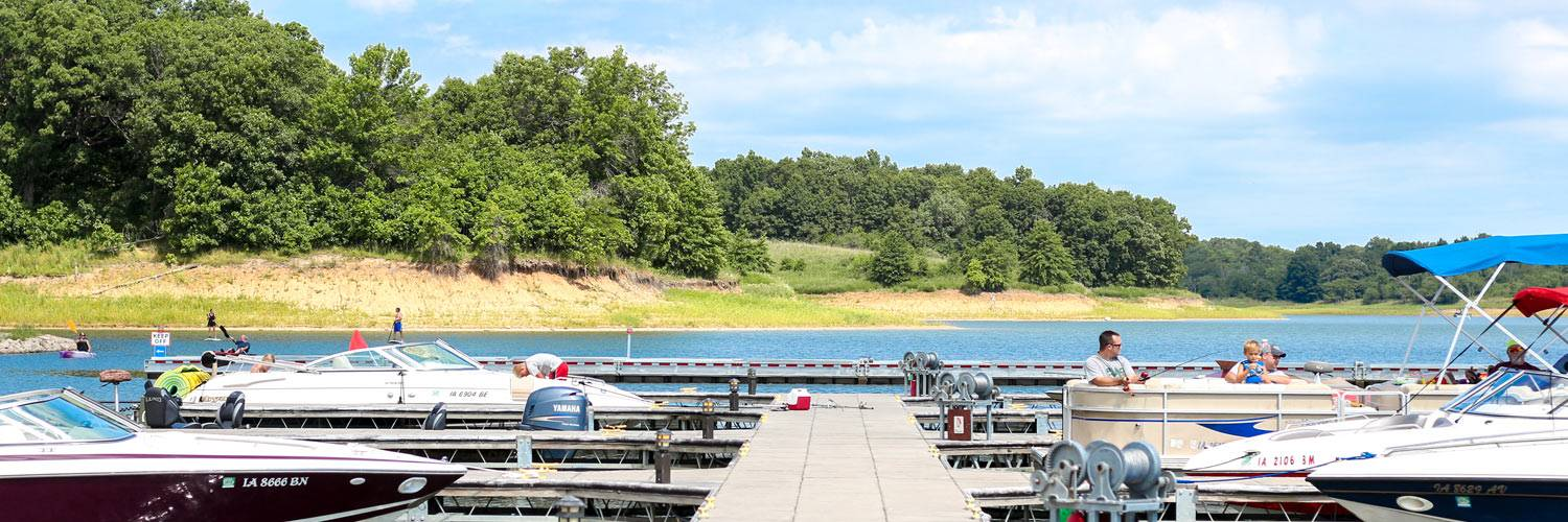 A marina with pontoons and other boats is shown on Rathbun Lake at Honey Creek Resort