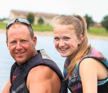 Father and daughter sitting on a jet ski wearing life jackets