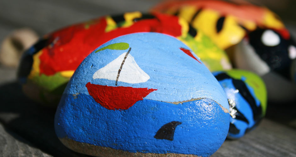 Several painted rocks including one with a sailboat and water